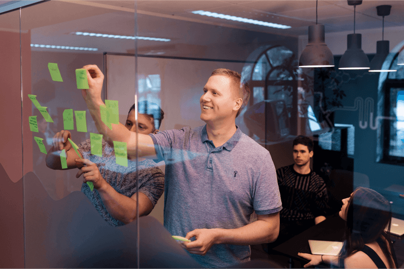 Alex attaching a post-it to a glass wall