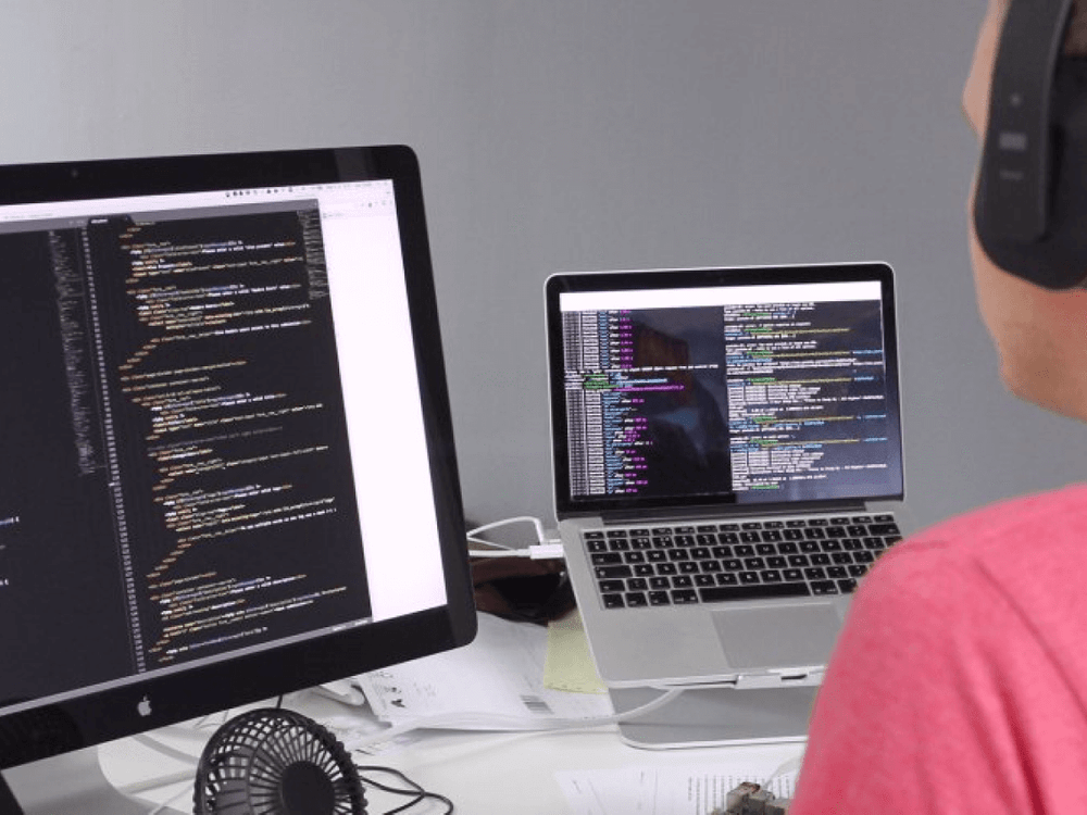 A developer looking at his code on two monitors