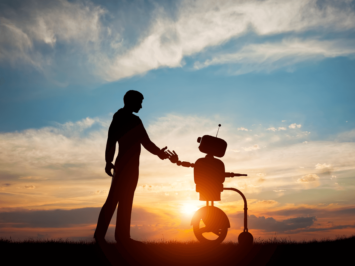 Man shaking hands with a robot with sunset in the background