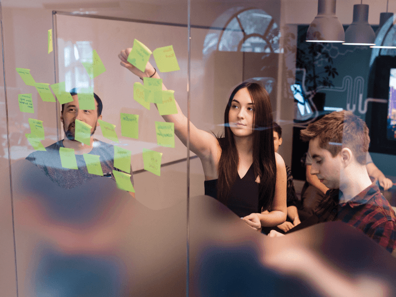 People pinning post-its to a glass wall